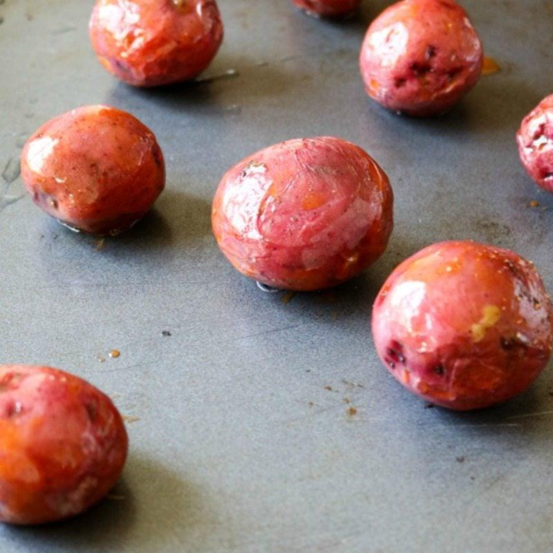 Red Potatoes on baking sheet with buffalo seasoning