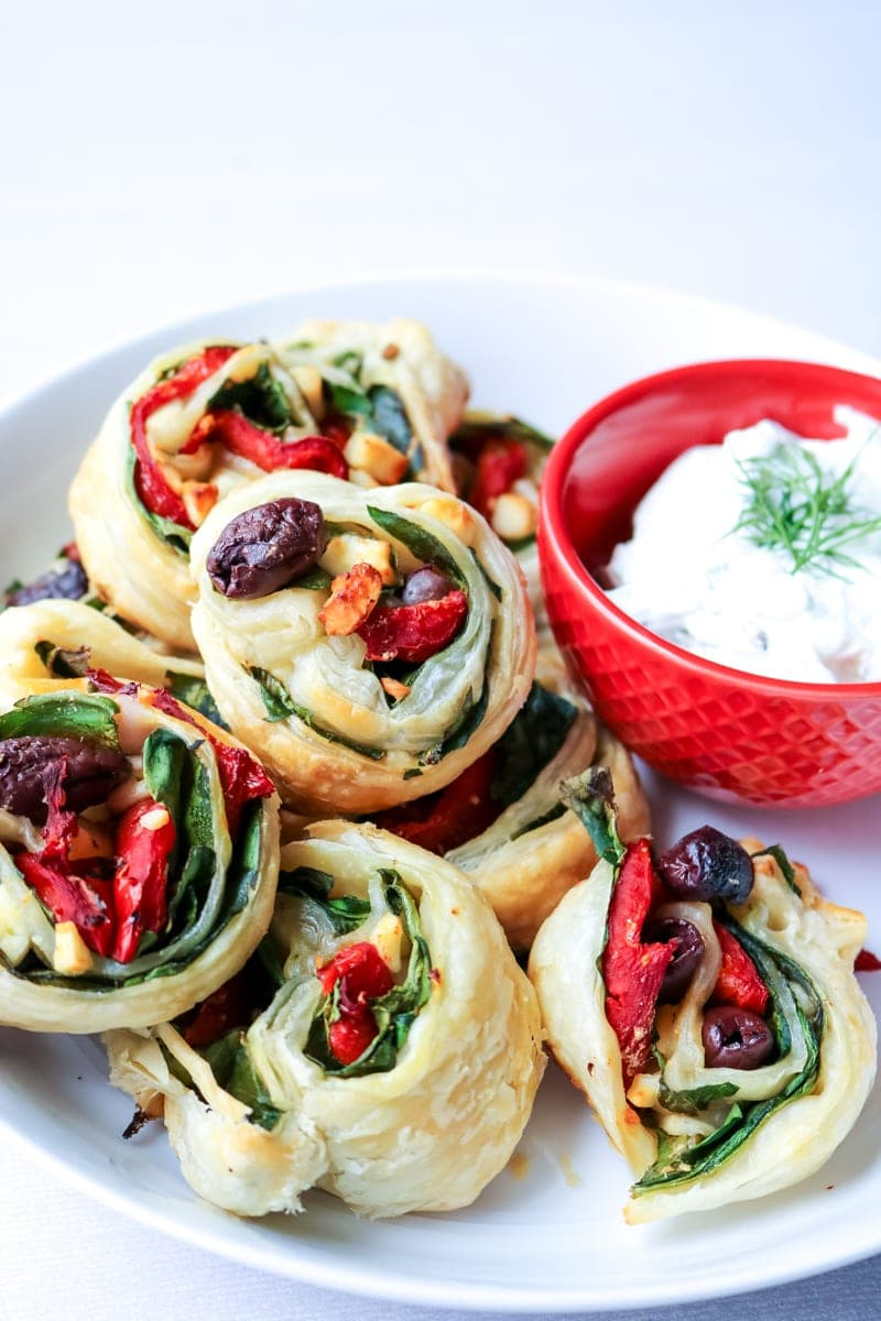 Simple Greek Pinwheels with Tzatziki Dipping Sauce: Spinach, roasted red peppers, olives, and feta are rolled up in buttery puff pastry and then served up with a Dill Tzatziki sauce.