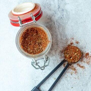 Jar with homemade cajun seasoning next to measuring spoon