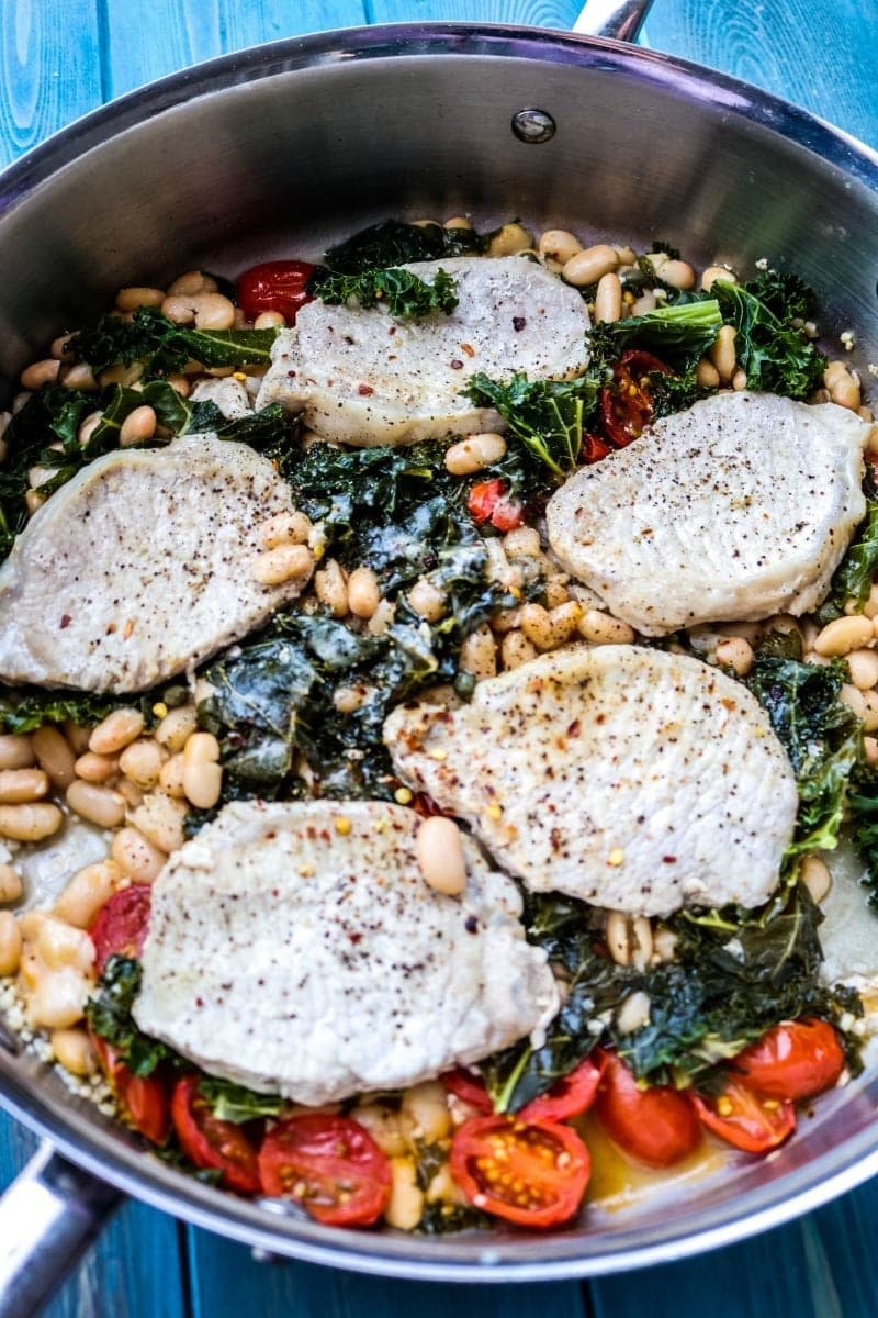Pork Cutlets braised with white wine, capers, tomatoes, kale and white beans.