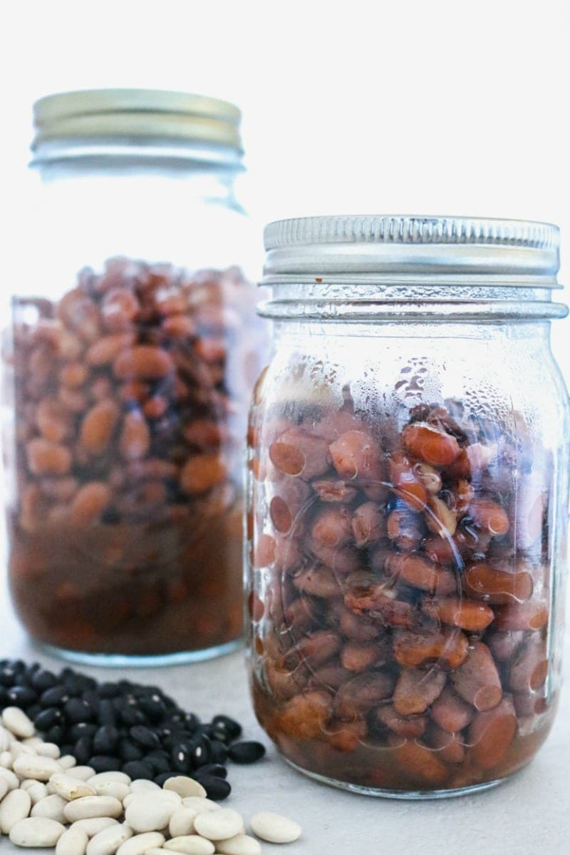 2 ball jars filled with cooked pinto beans that have dried beans off the side.