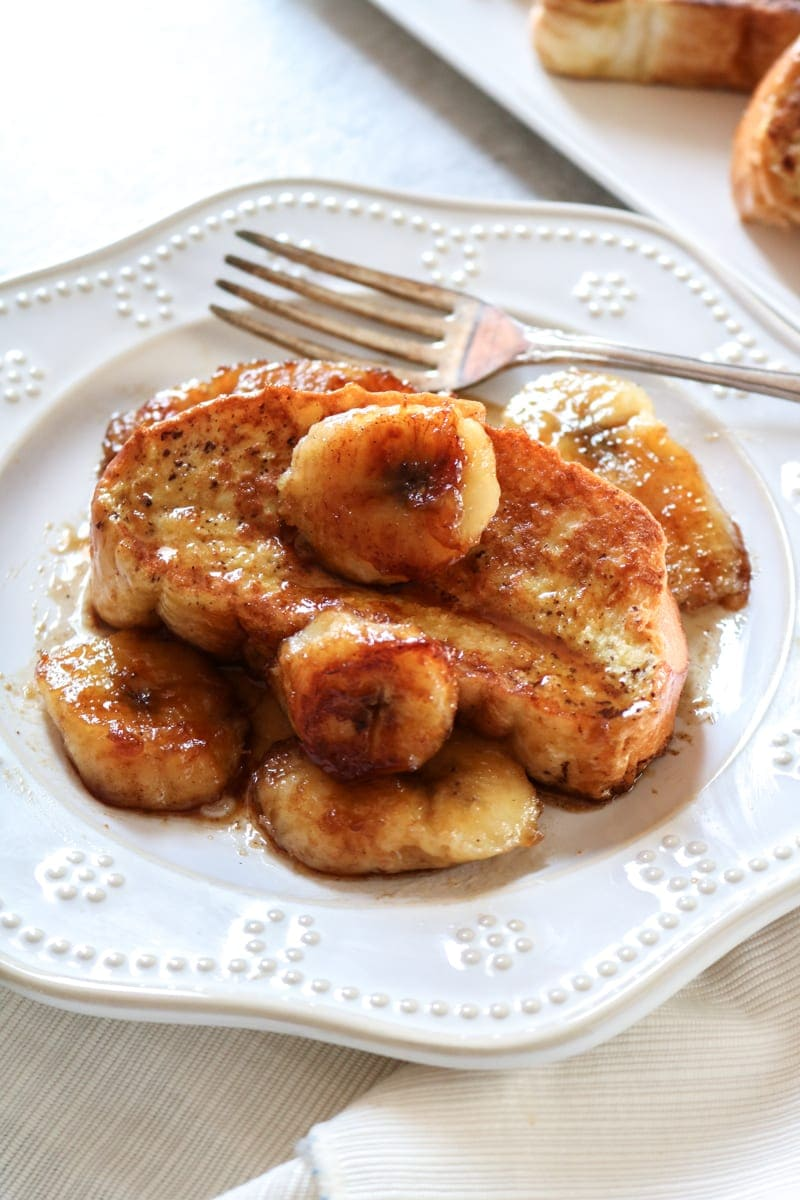 Bananas Foster French Toast on white plate topped with caramelized bananas