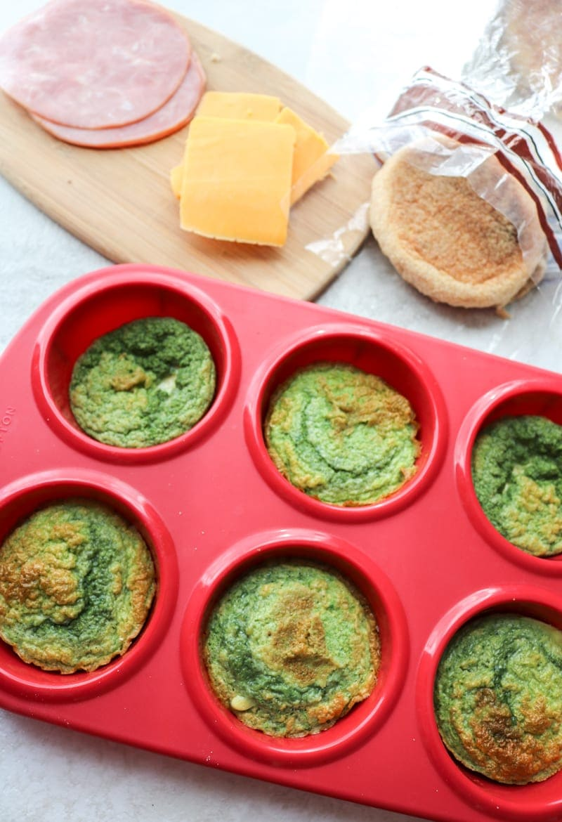 Muffin tin with spinach eggs next to whole wheat english muffins