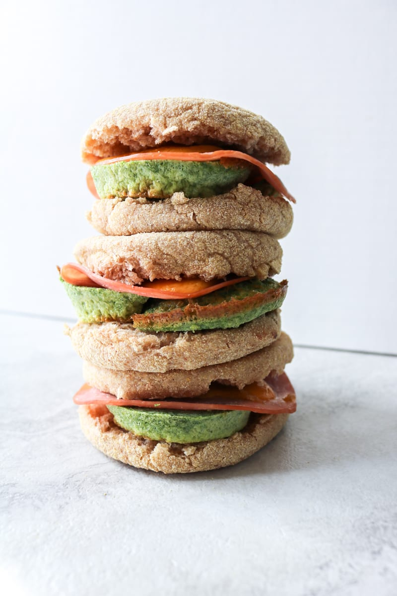 "Green Eggs and Ham Breakfast Sandwiches: Naturally ""dyed"" with spinach eggs are paired with ham and sharp cheddar cheese to create a breakfast sandwich."