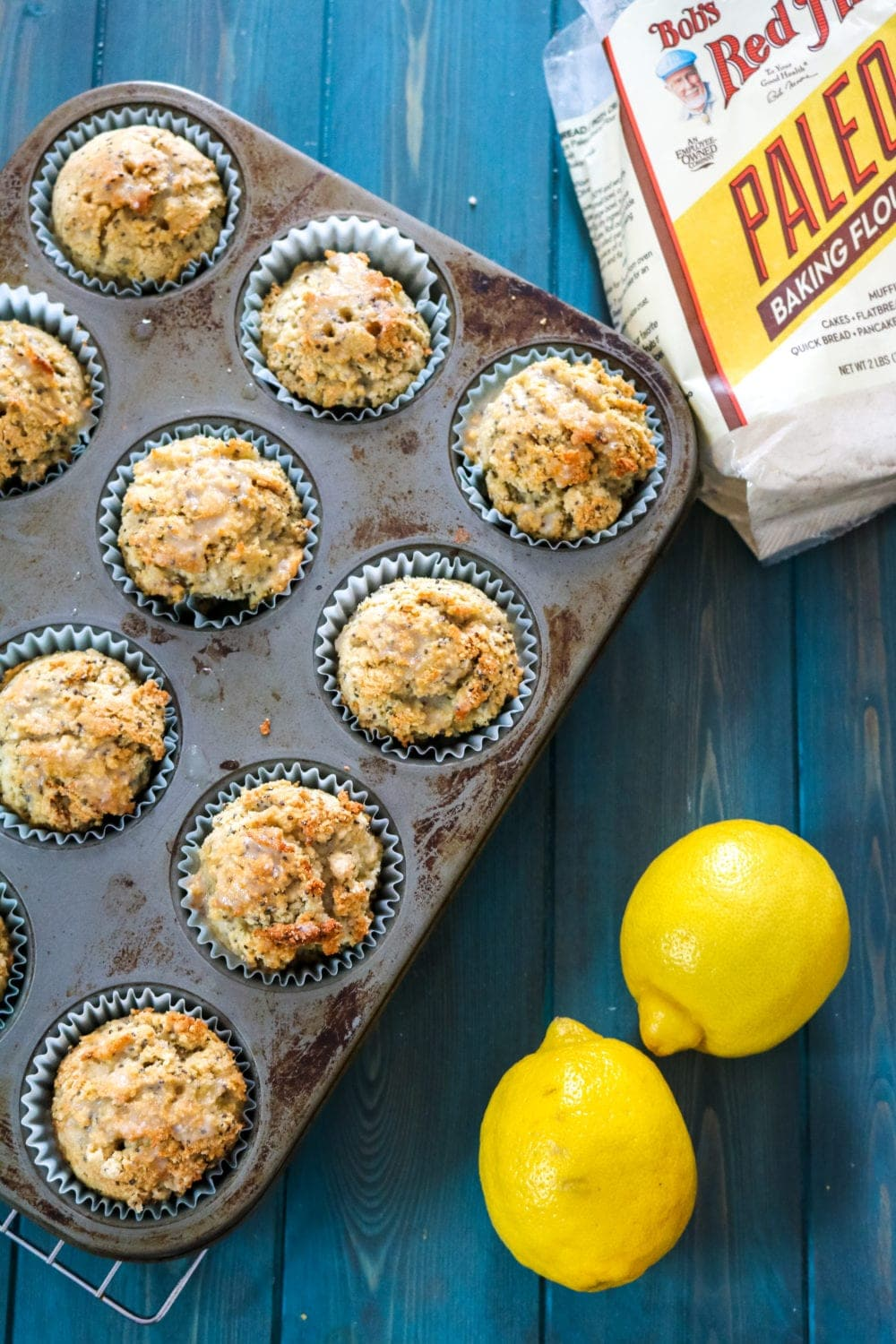 Coconut Lemon Muffins baked in muffin cup with paleo flour blend next to baking tray