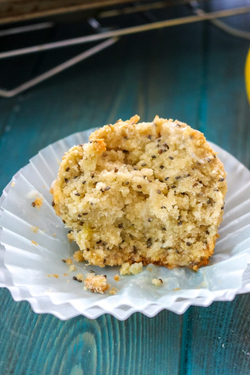 Paleo lemon muffin cut in half revealing lemon zest and chia seeds scattered in muffin