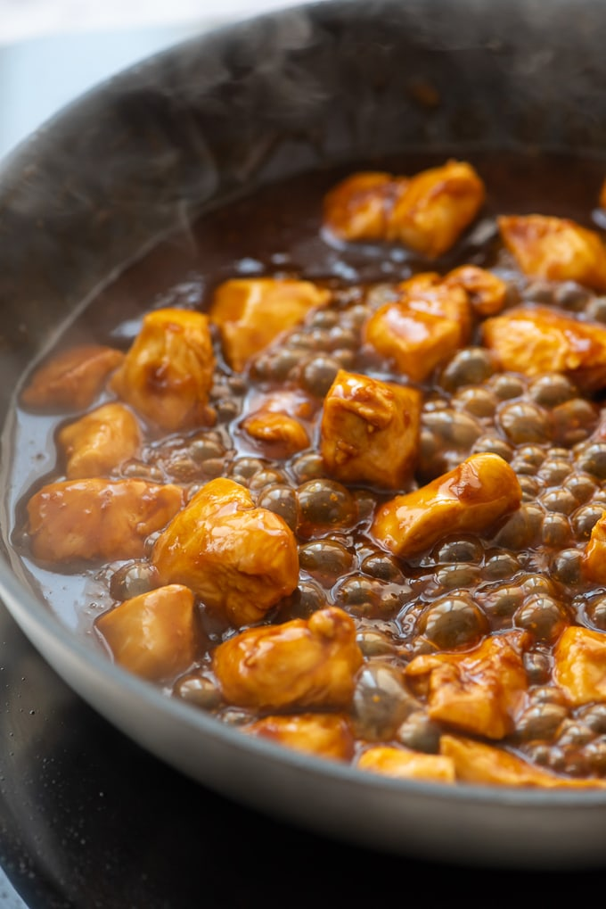 Skillet with orange chicken bubbling in sauce.