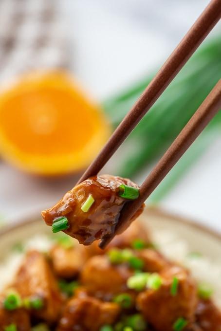 Chopstick holding piece of orange chicken