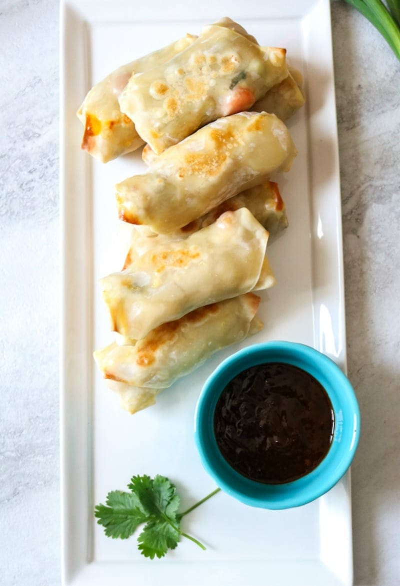 Crispy Pad Thai Egg Rolls on white platter with cilantro