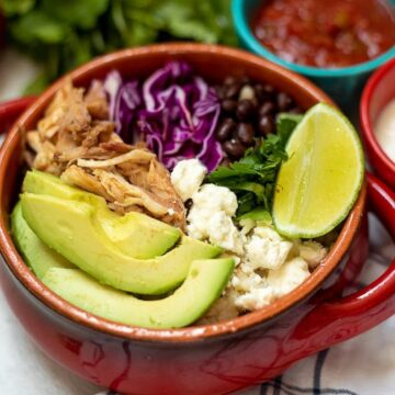 Red bowl with rice, shredded pork, avocado, cabbage and cheese