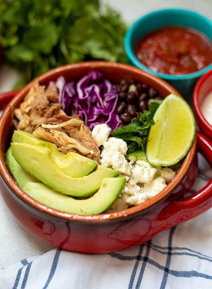 Red Bowl with rice, shredded pork, beans, lime, avocado