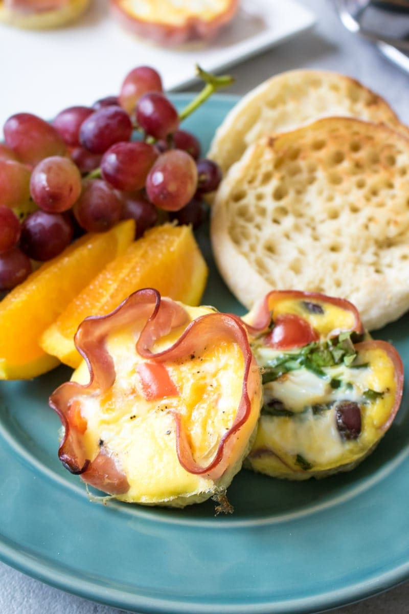 ham and egg muffin cups on a blue plate with fruit