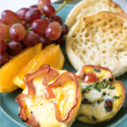 Eggs baked into slices of ham on blue plate with fruit and english muffin