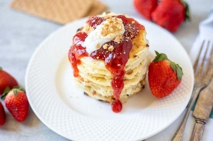 Plate of cheesecake pancakes with fresh strawberry sauce
