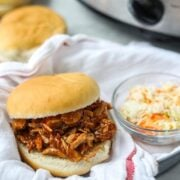 Pulled Pork Sandwich with coleslaw in basket next to slow cooker