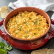 Red skillet of creamy Mexican corn dip
