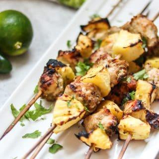 Jerk Chicken Kabobs on white platter next to limes