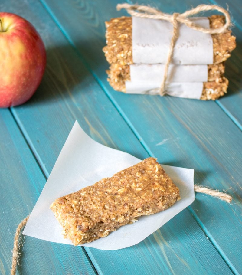 No bake apple granola bar on piece of parchment paper next to apple