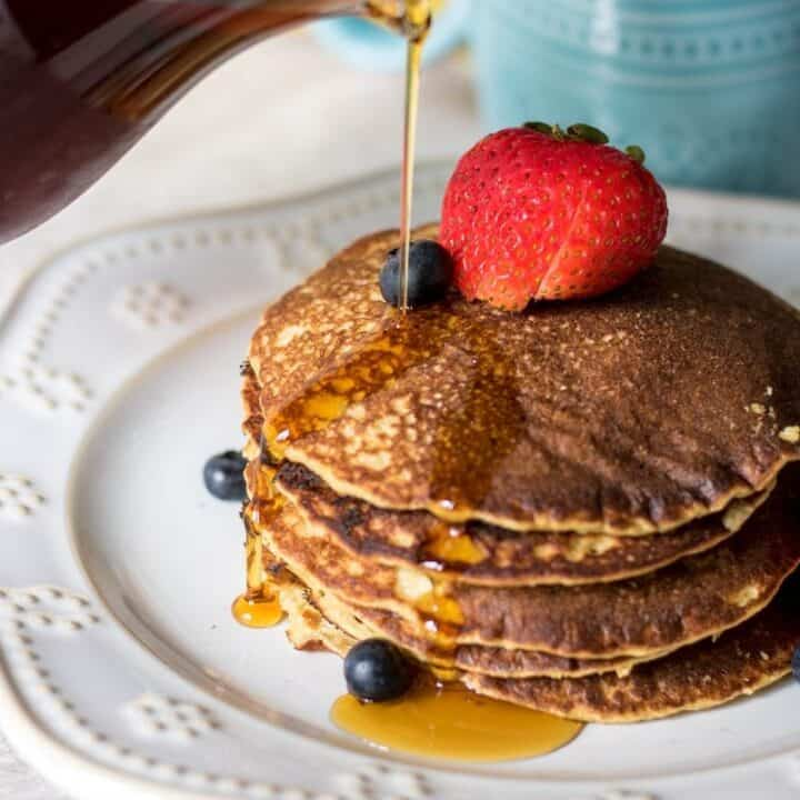Healthy Pancakes with syrup being poured on them. Gluten free oatmeal blender pancakes