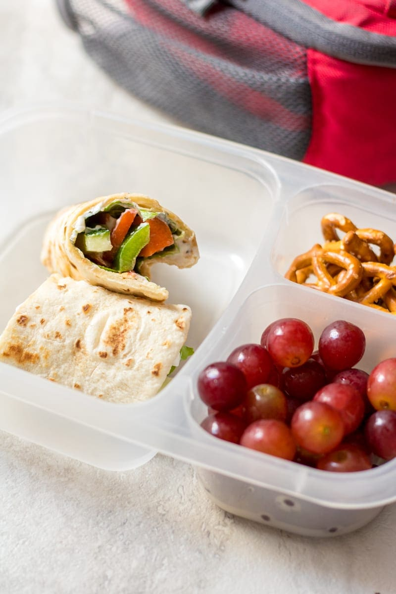 Ranch Veggie Wrap in lunch box container with grapes and pretzels