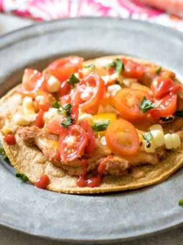 Southwestern Veggie Tostadas on silver plate topped with tomatoes and and corn