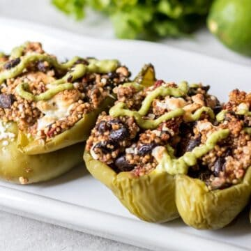 Quinoa Stuffed Peppers on white platter topped with avoacado cream