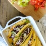 Easy 15 Minute Gluten Free Tacos--Black bean mixure topped with white sharp cheese are baked in white dish and then served with chopped lettuce and tomatoes on the side.