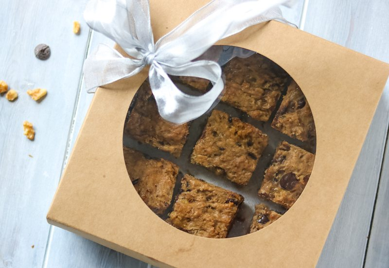 A box of wrapped Chocolate Chip Peanut Butter Banana Bars with a silver bow--a perfect gift to give someone you love or to say thank you to.