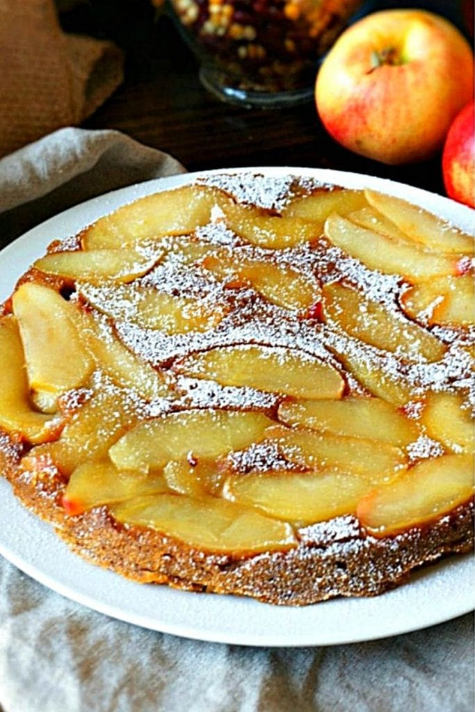 Pumpkin Apple Cake on White platter dusted with powdered sugar