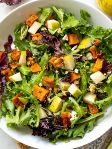 A blue pottery bowl filled with baby mixed greens, roasted butternut squash, pear cubes, feat and dried cranberries.