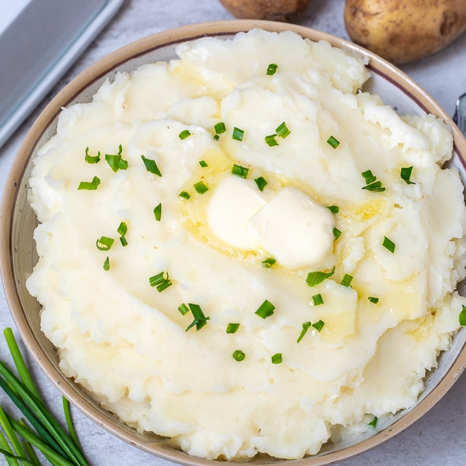 Bowl of Creamy Mashed Potatoes topped with butter and chives