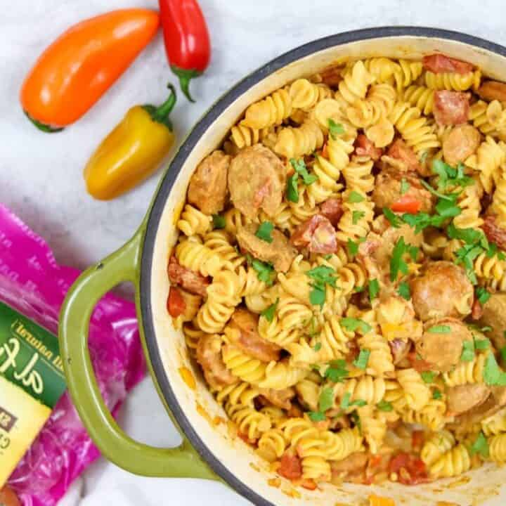 Pan with cooked cajun pasta next to peppers and package of sausage