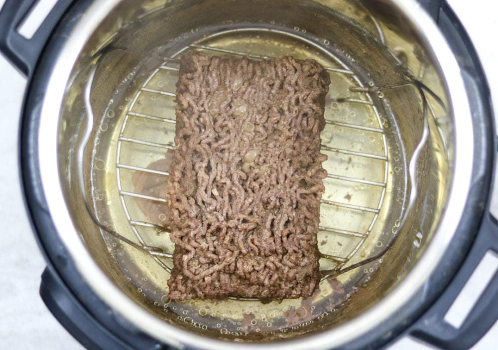 Cooked ground beef inside of the Instant Pot on metal rack.