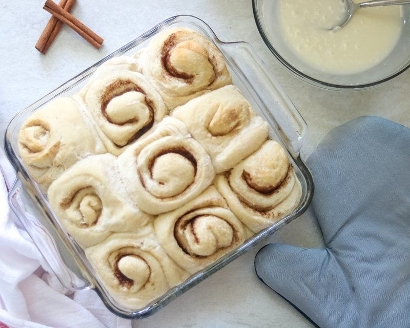 Baked unfrosted cinnamon rolls in clear 8x9 baking dish.