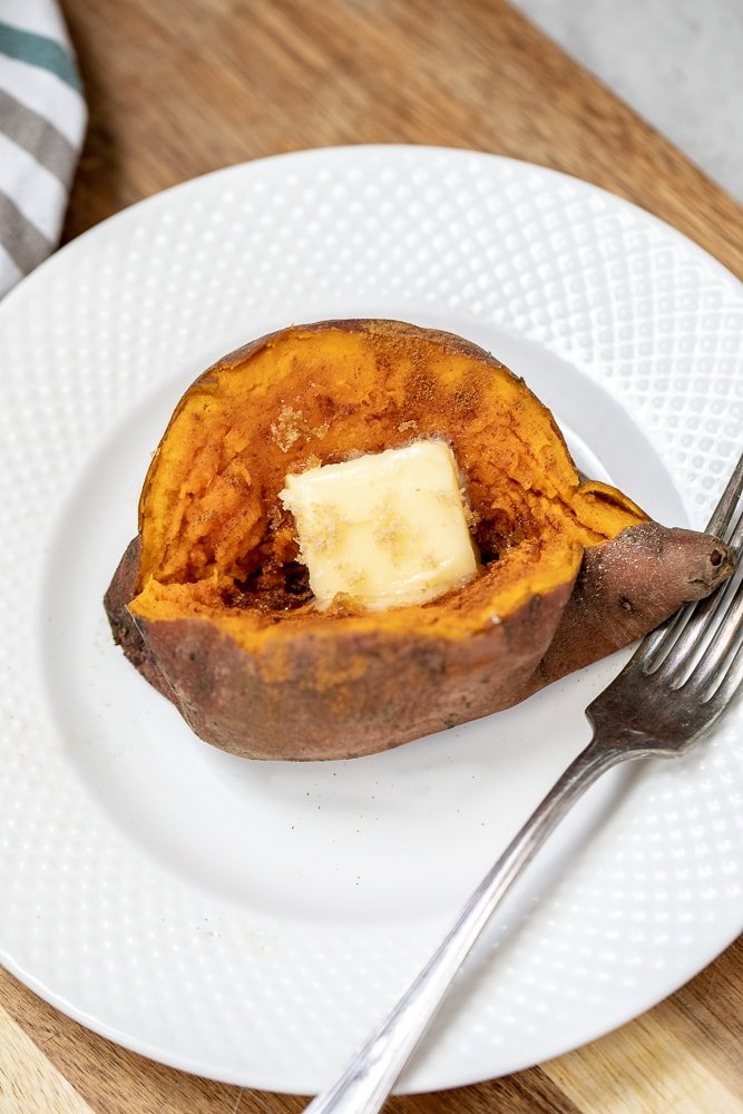 Baked Sweet Potato on white plate topped with butter and cinnamon