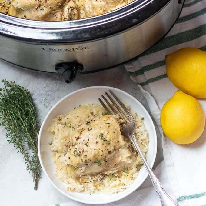 Bowl of lemon garlic rice with chicken thighs next to crock pot