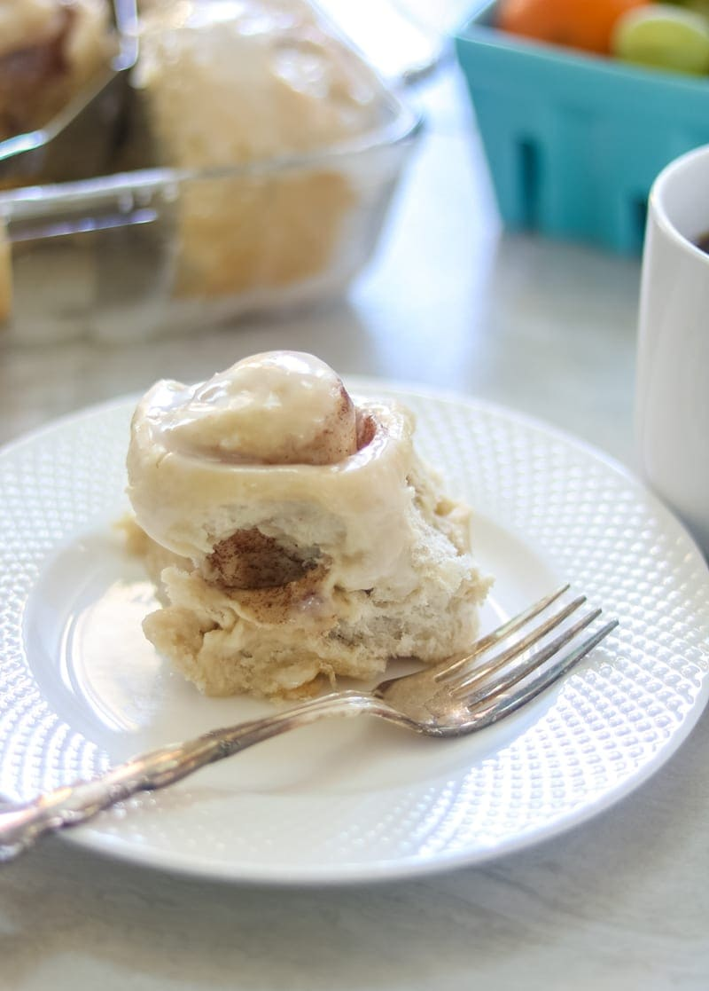 Side view of fluffy baked skinny cinnamon roll on white plate with fork off to side