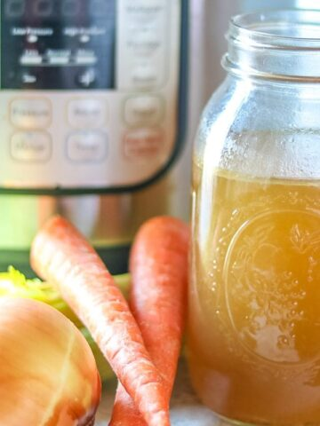 Bone Broth sitting next to Instant Pot and Carrots and Onions