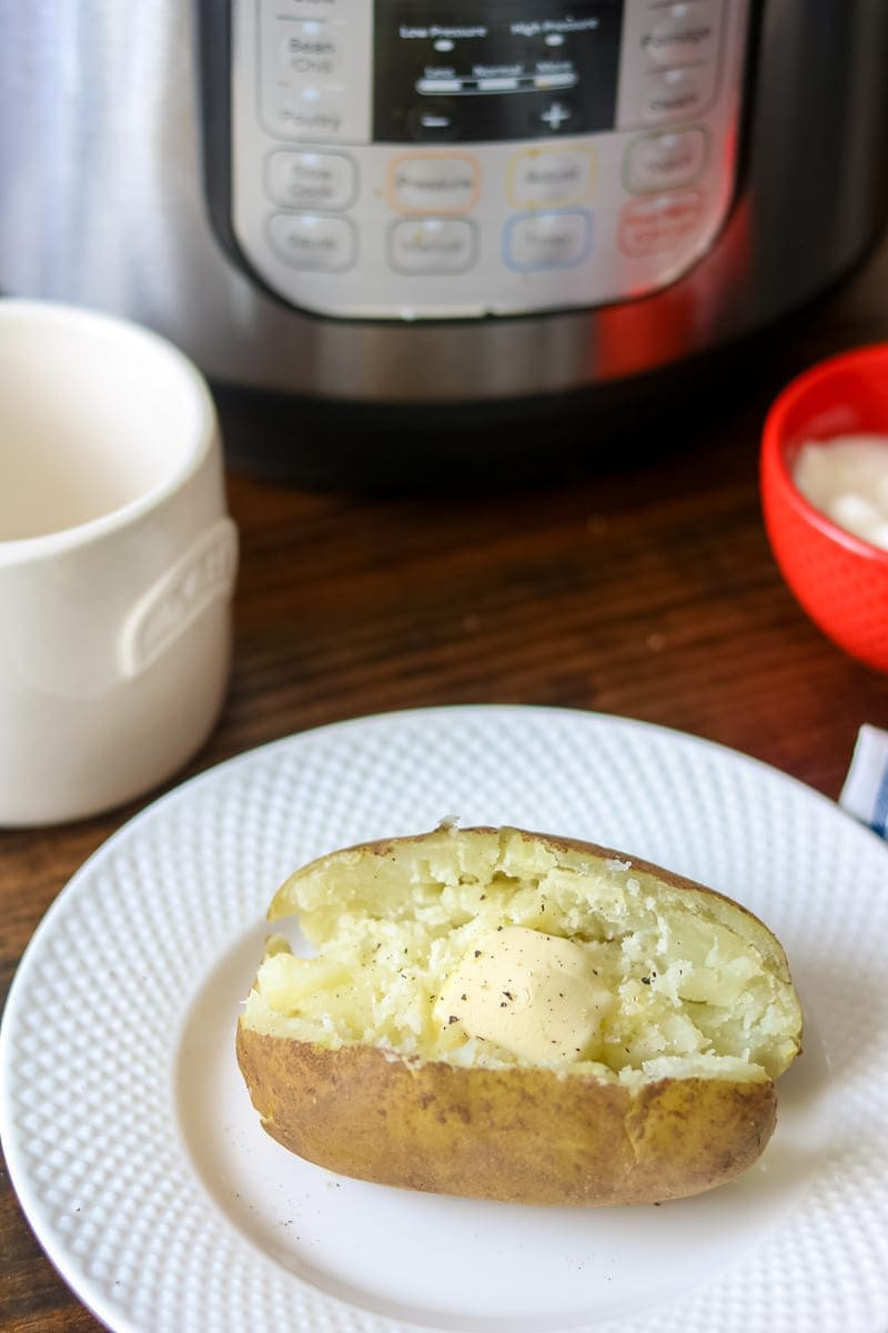 Fluffy baked potato on white plate with Instant Pot in Background.