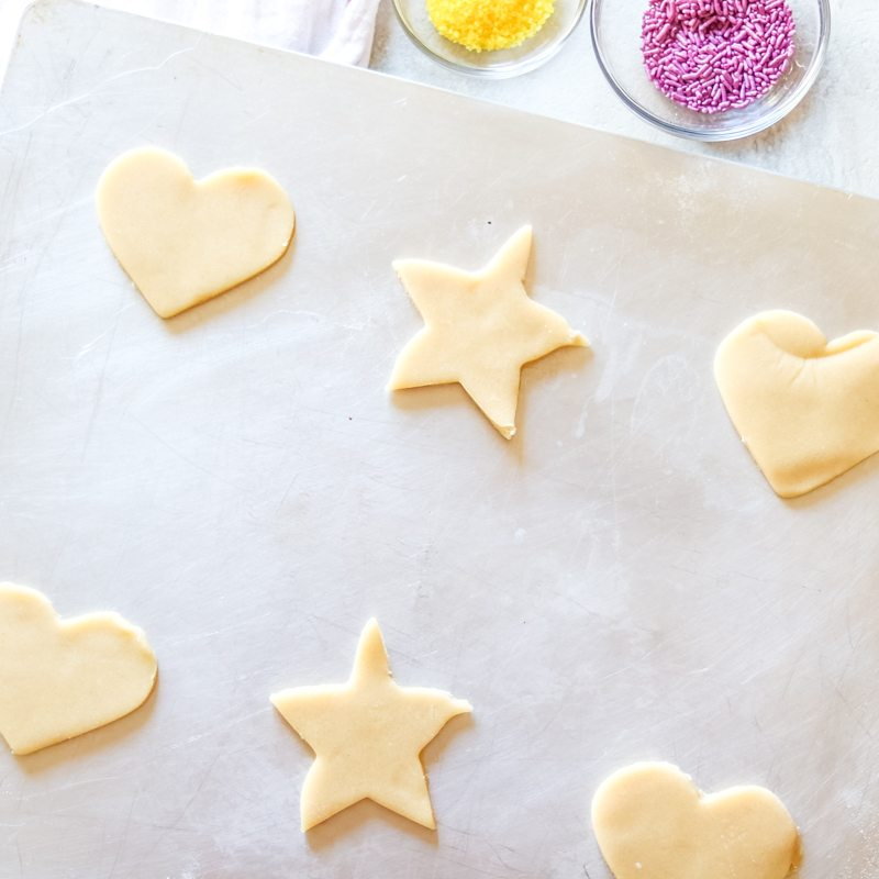 Chilled Sugar Cookie Dough that has been cut out into simple shapes and ready to bake.