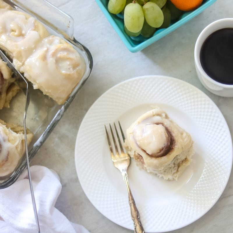 Easy Skinny Overnight Cinnamon Rolls on a white plate with baked rolls to the side, a cup of coffee to the right and fresh fruit in a blue basket.