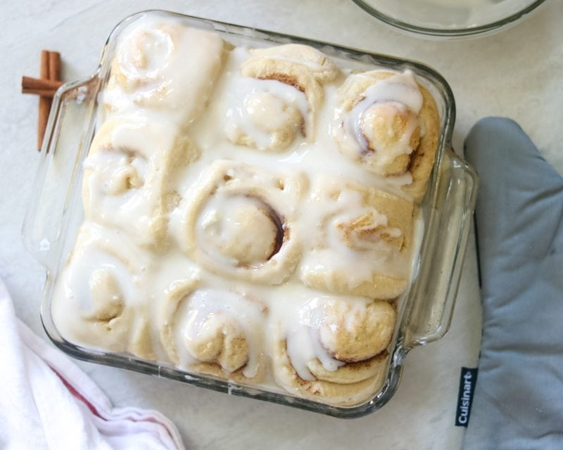 Pan of perfectly golden skinny cinnamon rolls made with whole grain flour and a smothered in a light cream cheese glaze