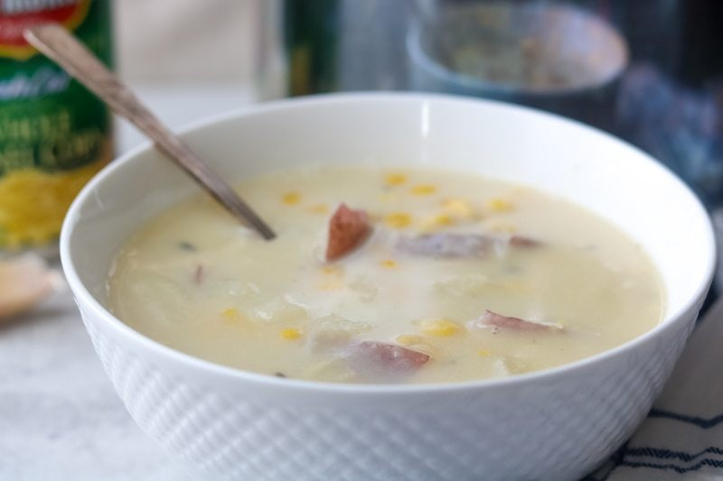 Side view of white bowl filled with hearty, thick Corn Chowder with red potatoes.