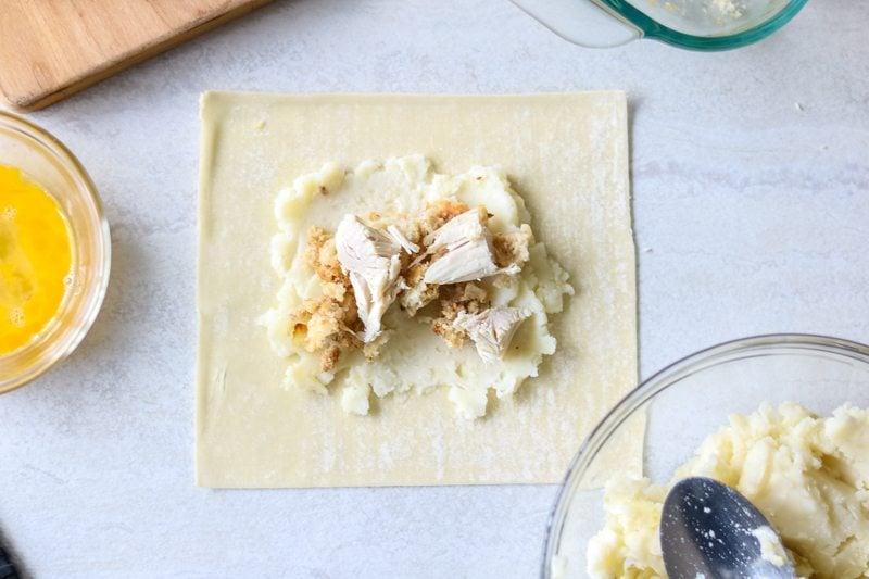 Adding leftover roasted turkey to a wonton wrapper to make leftover Thanksgiving Egg Rolls