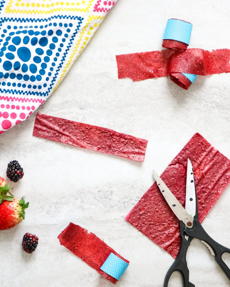 Homemade strawberry fruit roll ups on white board with scissors and fruit scattered around