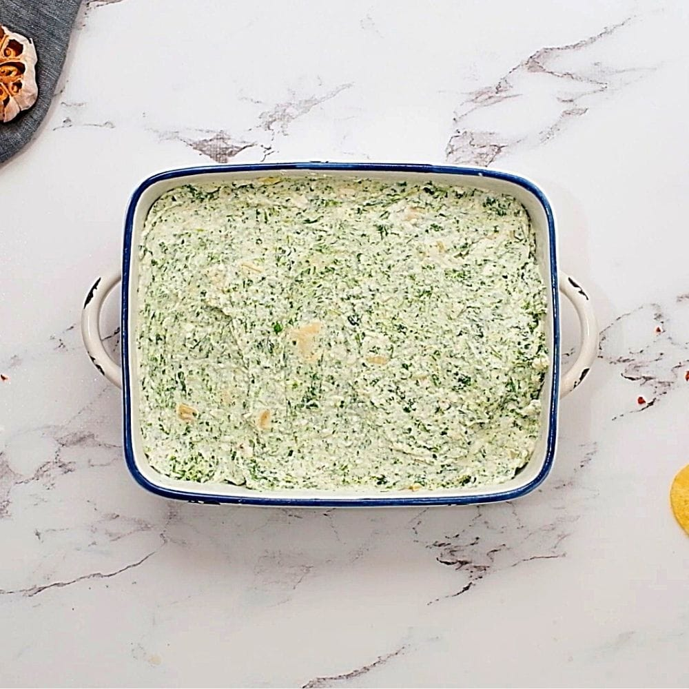 Unbaked spinach artichoke dip in baking dish