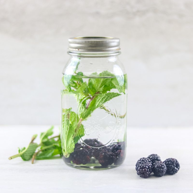 Ball glass jar filled with mint sprgs and blackberries for blackberry mint water.