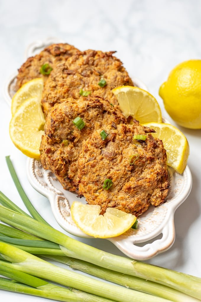 Baked tuna patties on white plate with lemons and green onions