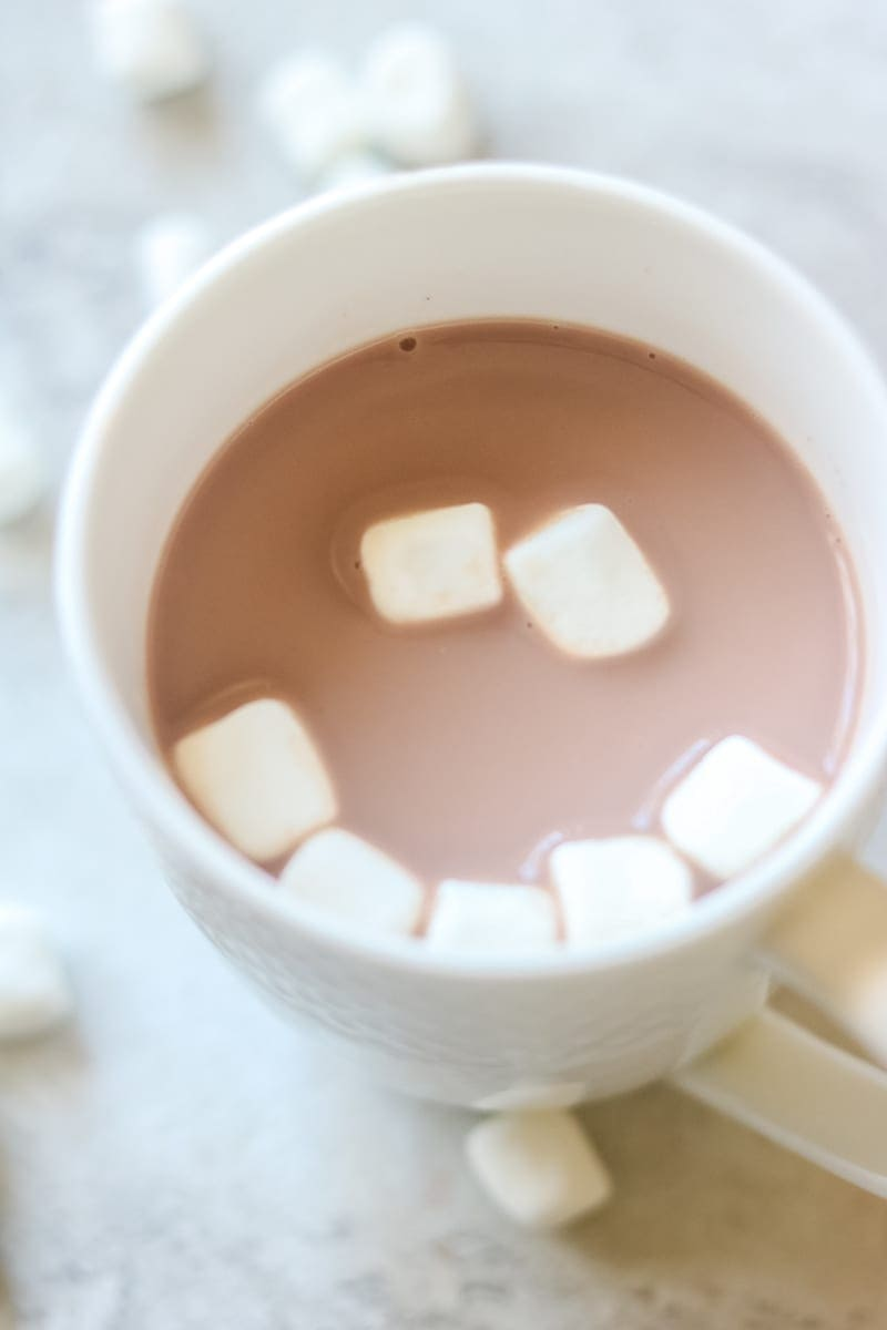 White mug filled with hot chocolate topped with a mini-marshmallows in shape of a smile.