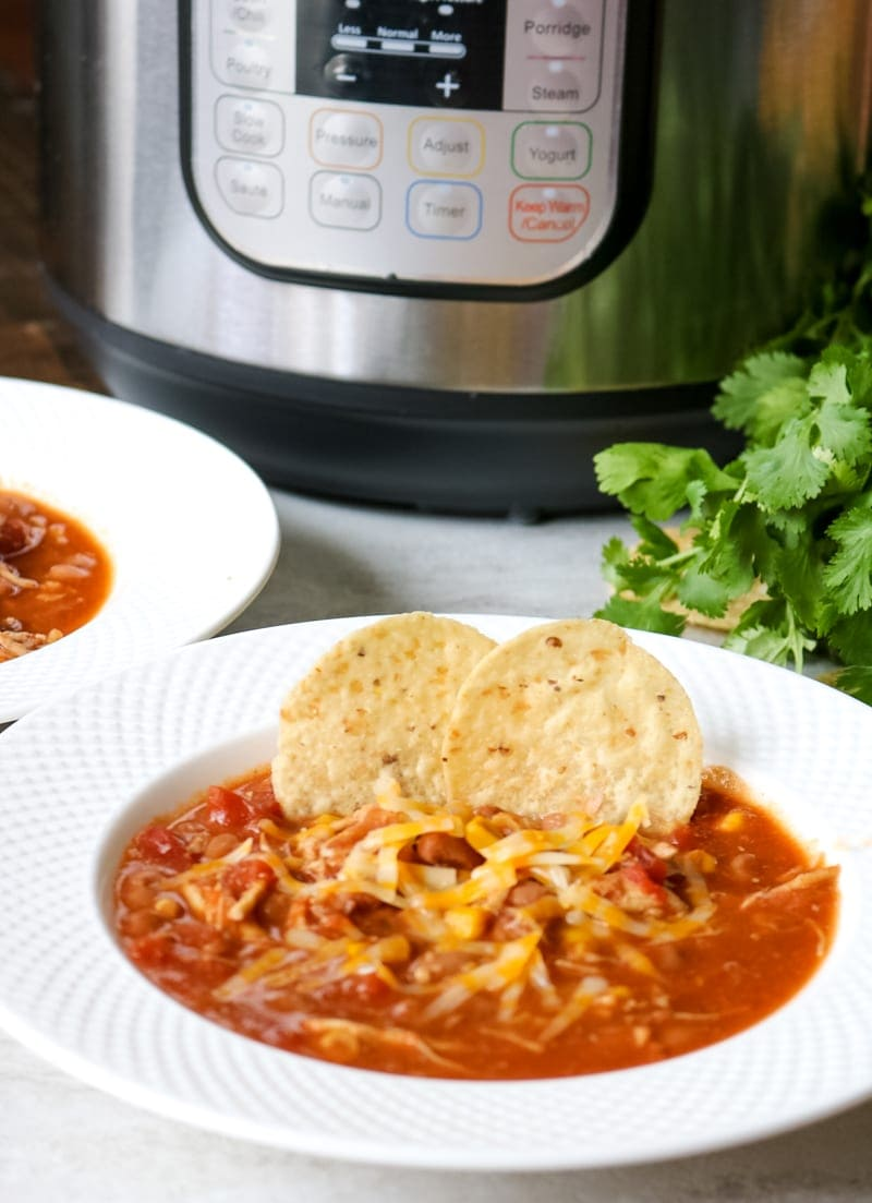 Instant Pot in background with chicken chili served up in white bowl with tortilla chips